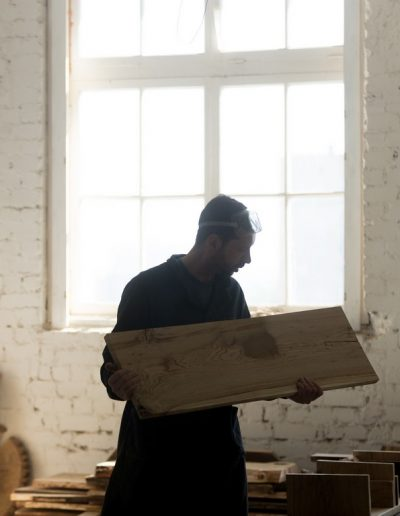 Young carpenter holding wooden board, woodworking in carpentry s